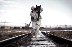 Soldat trägt einen Hund auf schwierigem Geländer