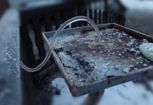 Gebogene Eissäule aus einem gefrorenen Metallrohr